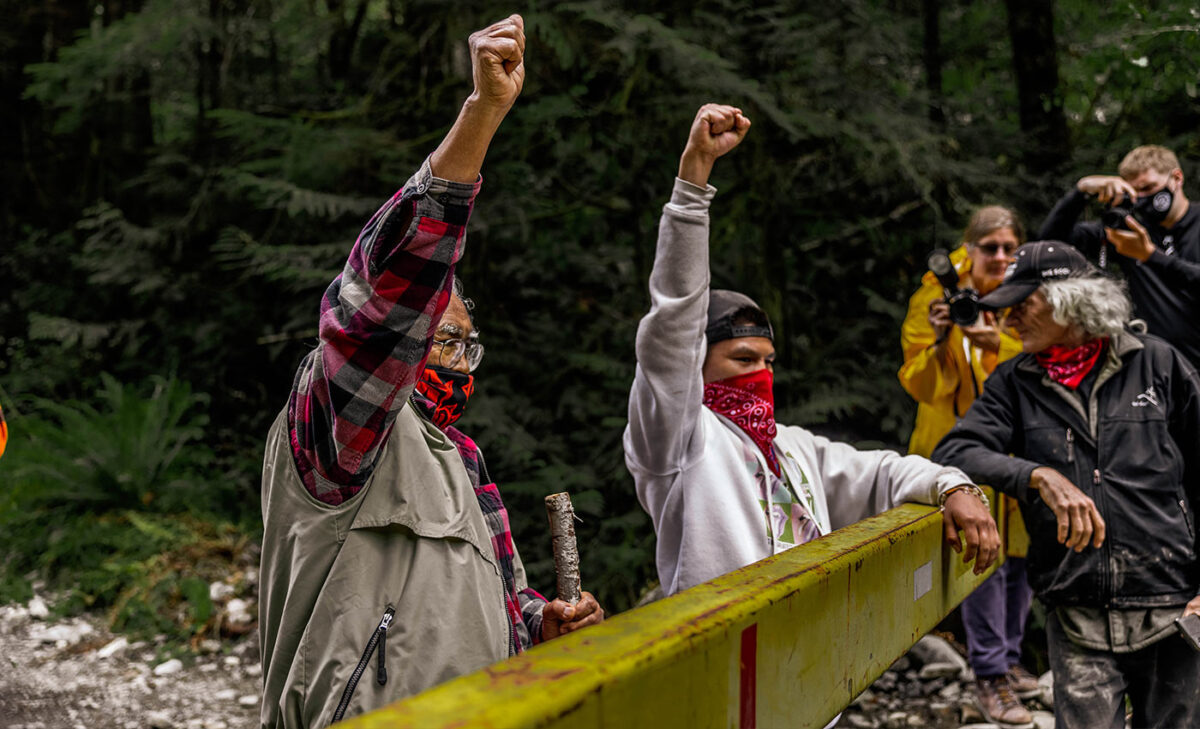 Pacheedaht Elder Bill Jones and Hereditary Chief Victor Peters at a gate with their fists in the air.