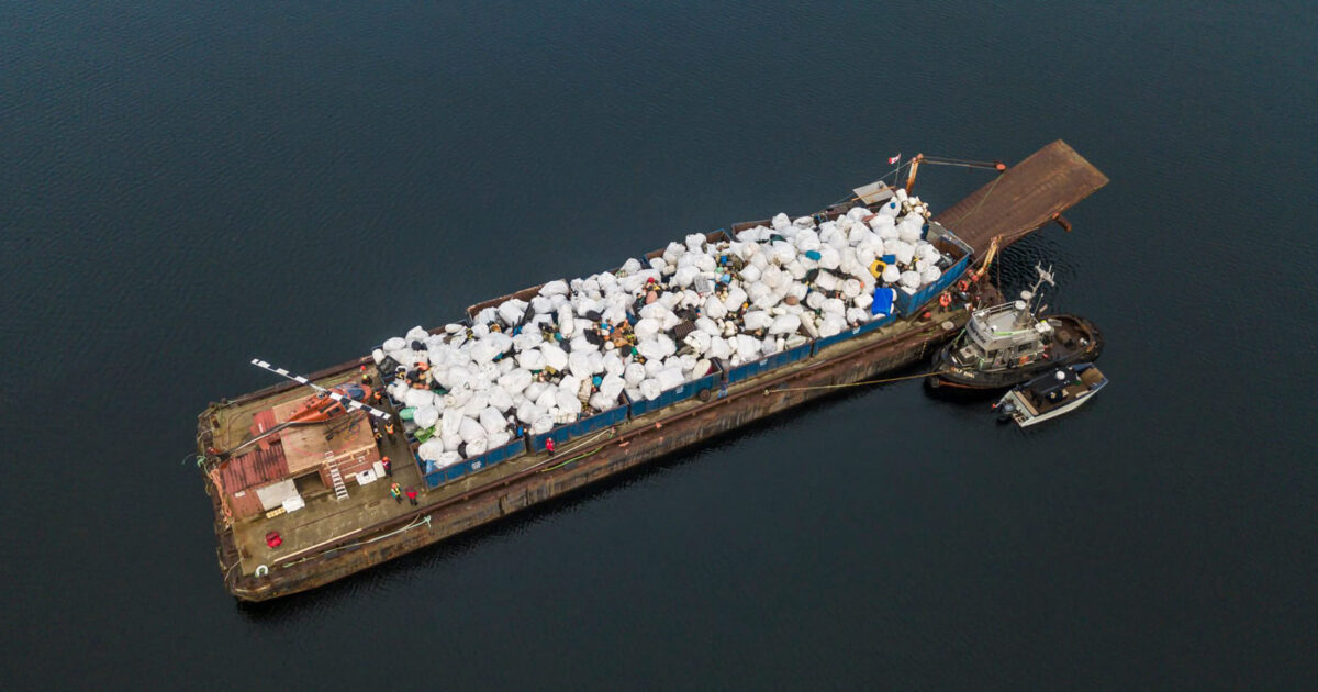 Drone photo of a barge filled with large garbage.