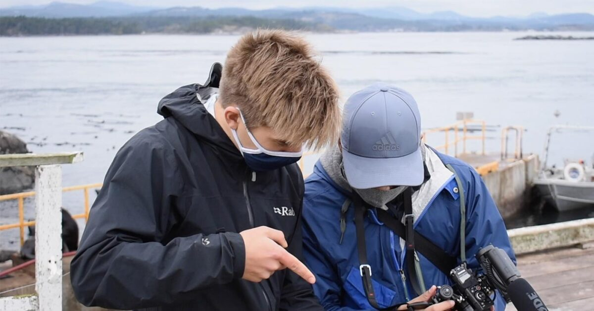 Two young men wearing masks looking at a camera screen with the ocean in the background.