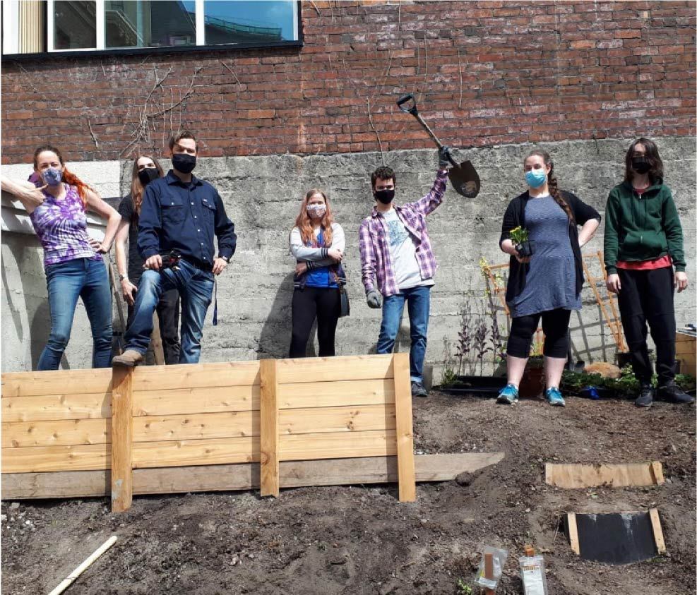 A group of students standing in front of garden boxes holding gardening tools.