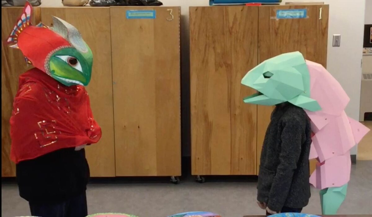 Two young people wearing salmon costumes in a classroom.