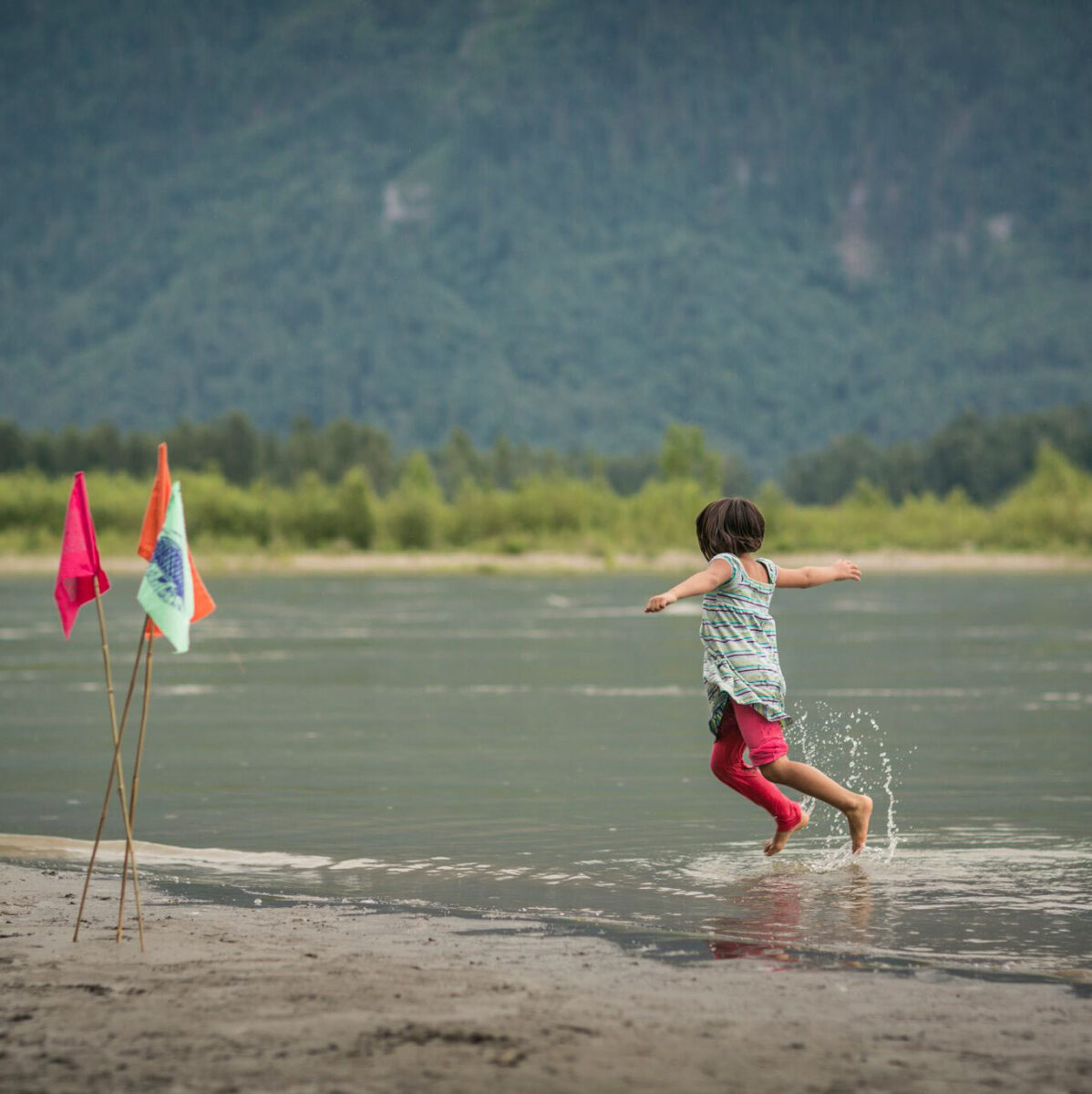 A young person jumps and plays splashing water in the Fraser River.