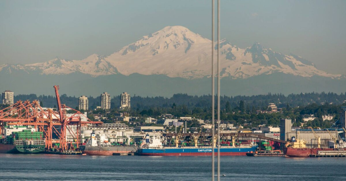 A view of the mountains over Vancouver, a layer of smog in the mid ground, and ships at rest in the foreground of the Salish Sea.