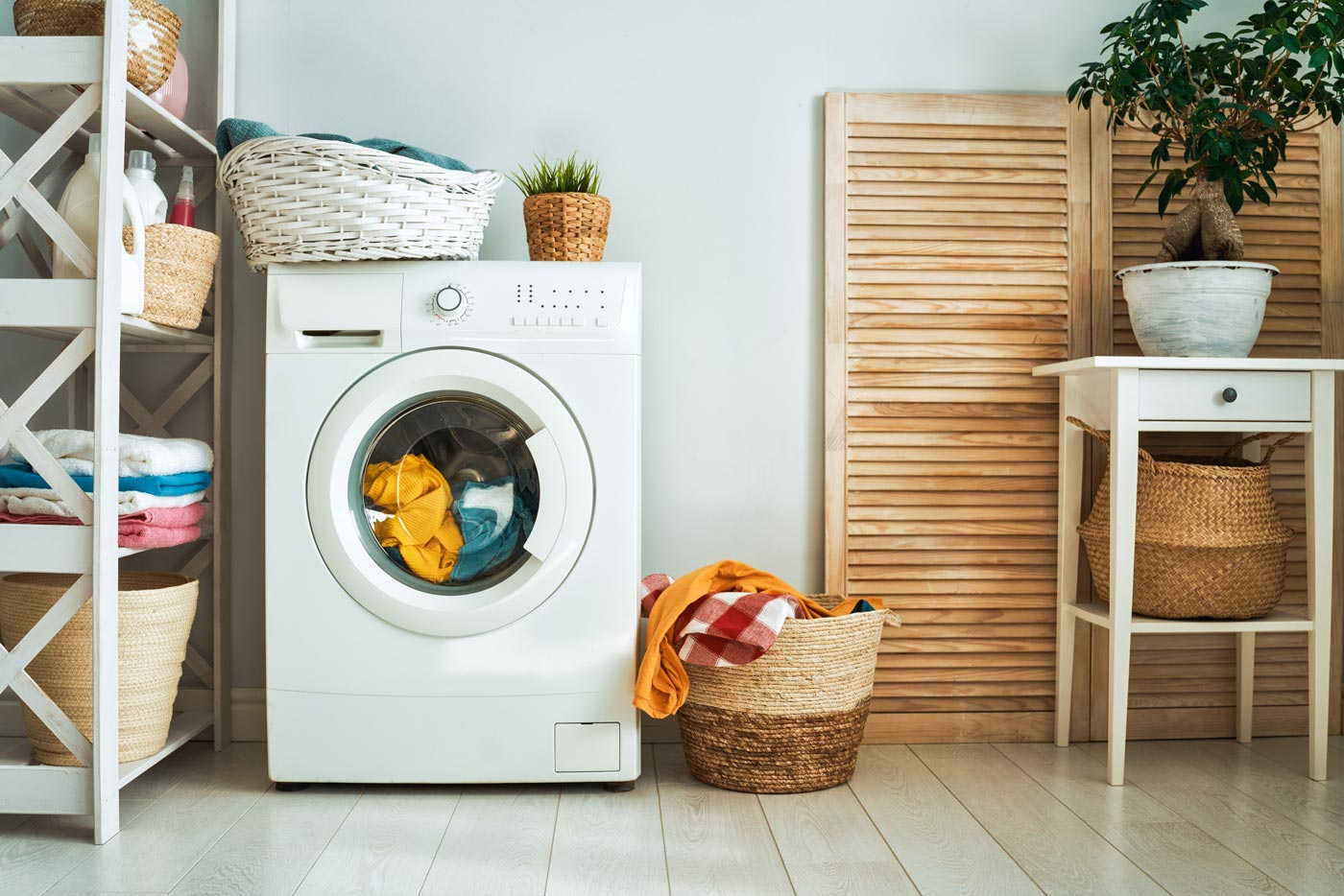 A washing machine sits full of laundry and conspicously absent is the dryer.