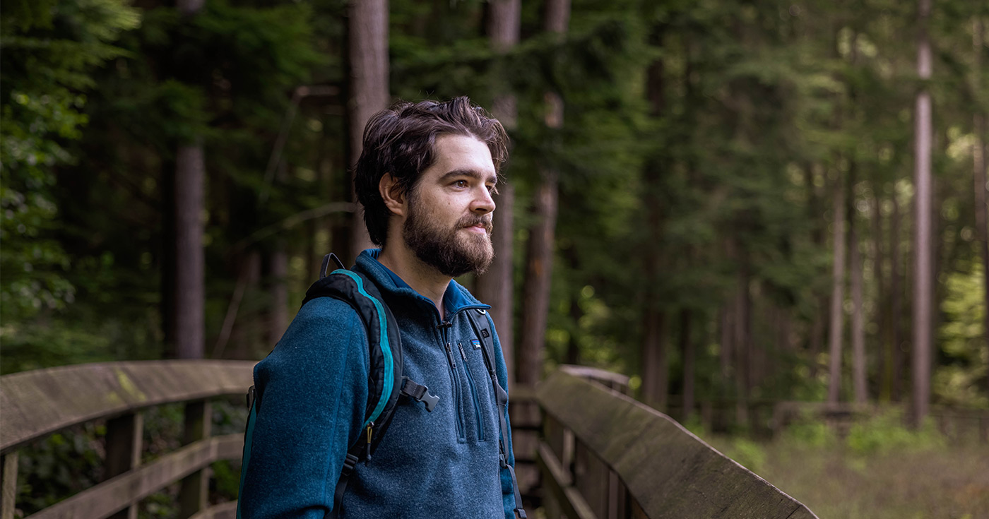 Riley Finn standing on a boardwalk in a forest looking out at a bog.