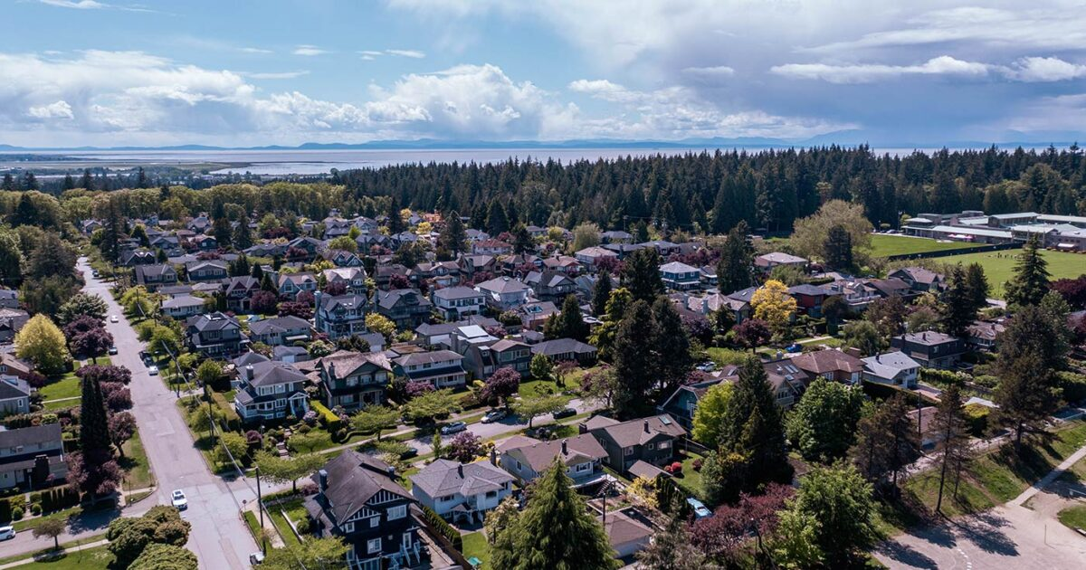 Drone image of a neighbourhood with the Fraser Estuary in the background.