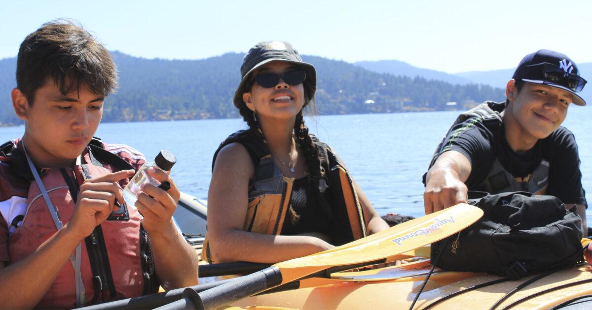 Three Salish Sea Emergin Stewards sit in their kayaks.