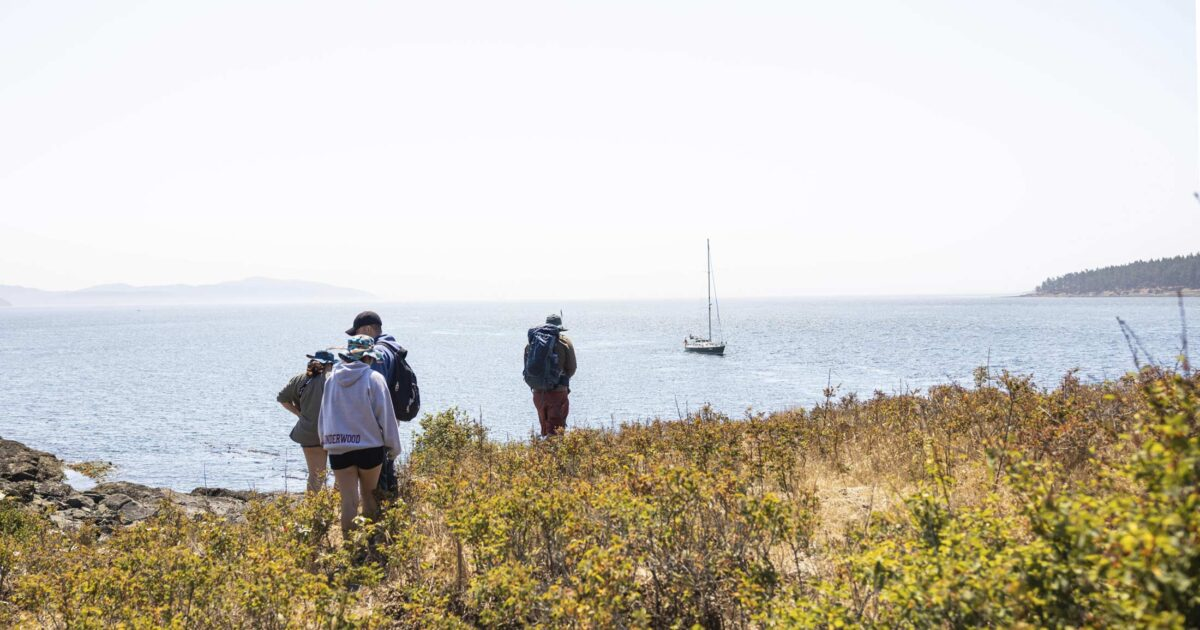 Salish Sea Emergin Stewards walk out toward the Salish Sea and Achiever.