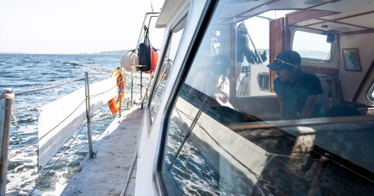Photo looking into our research boat, Achiever, with people inside.